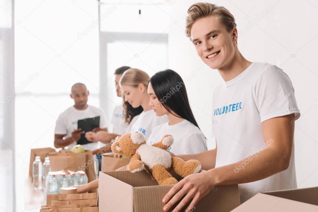 volunteer holding teddy bear and box
