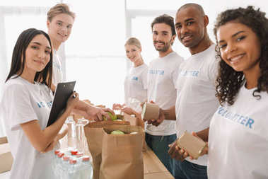 Multiethnic group of volunteers putting food and drinks in paper bags and looking at camera stock vector