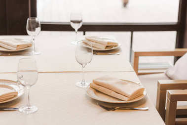 Served table with wineglasses and plates with napkins