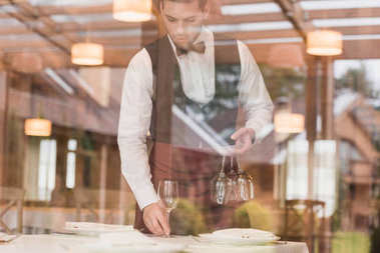 waiter putting wineglasses on table
