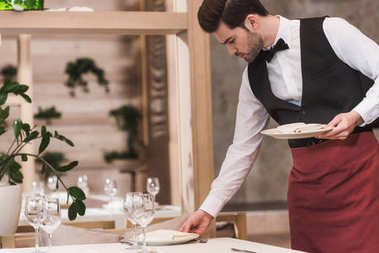 Waiter serving plates on table