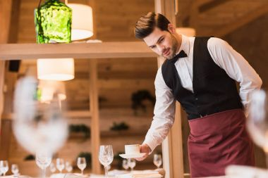 waiter serving cup of coffee