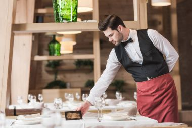 Waiter putting reserved sign on a table at the restaurant stock vector