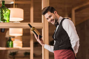 Smiling waiter showing bottle of red wine stock vector