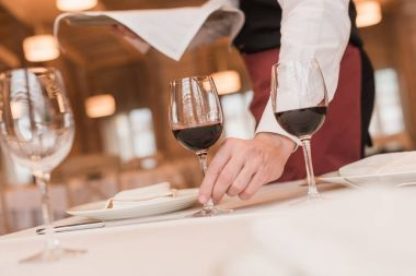 Cropped image of waiter serving glasses with red wine on table stock vector