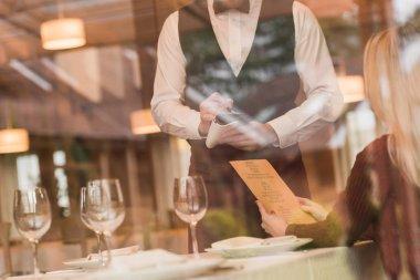 Waiter writing down the order of customer