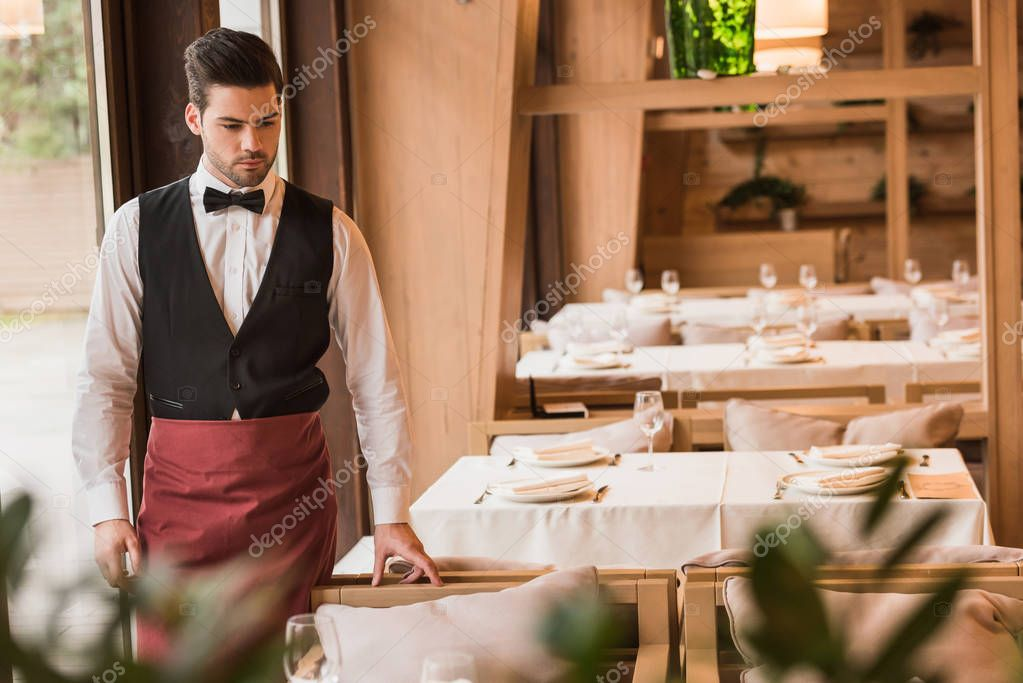 Waiter looking at served table