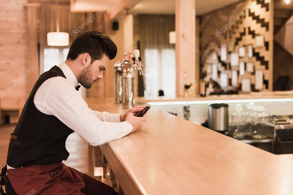 Waiter sitting at bar counter with smartphone