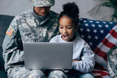 soldier and child using laptop