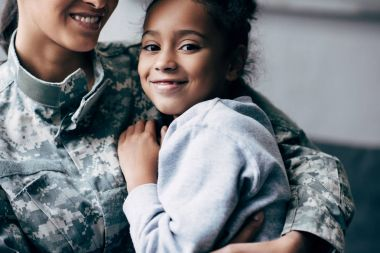 African american daughter hugging soldier in military uniform at home stock vector