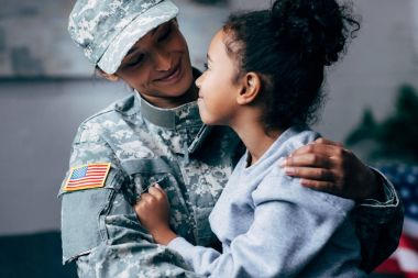African american daughter hugging mother in military uniform at home stock vector