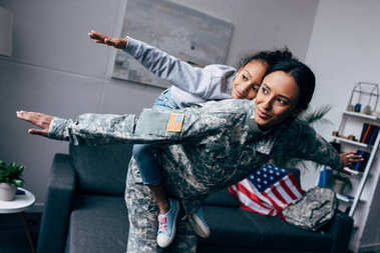 mother in military uniform piggybacking daughter