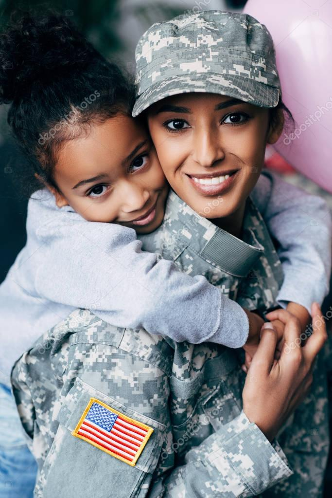 daughter hugging mother in military uniform