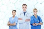 Chirurgové a lékaři s překřížením rukou
