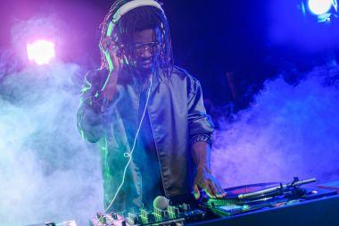 DJ in headphones with sound mixer