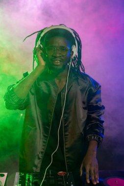 Professional african american club DJ in headphones with sound mixer in nightclub stock vector