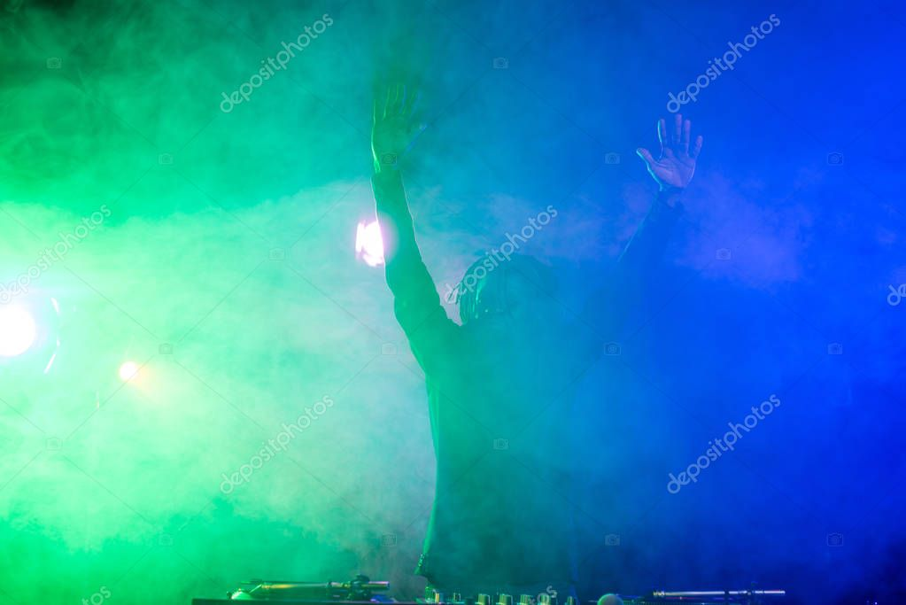 DJ in nightclub with back light