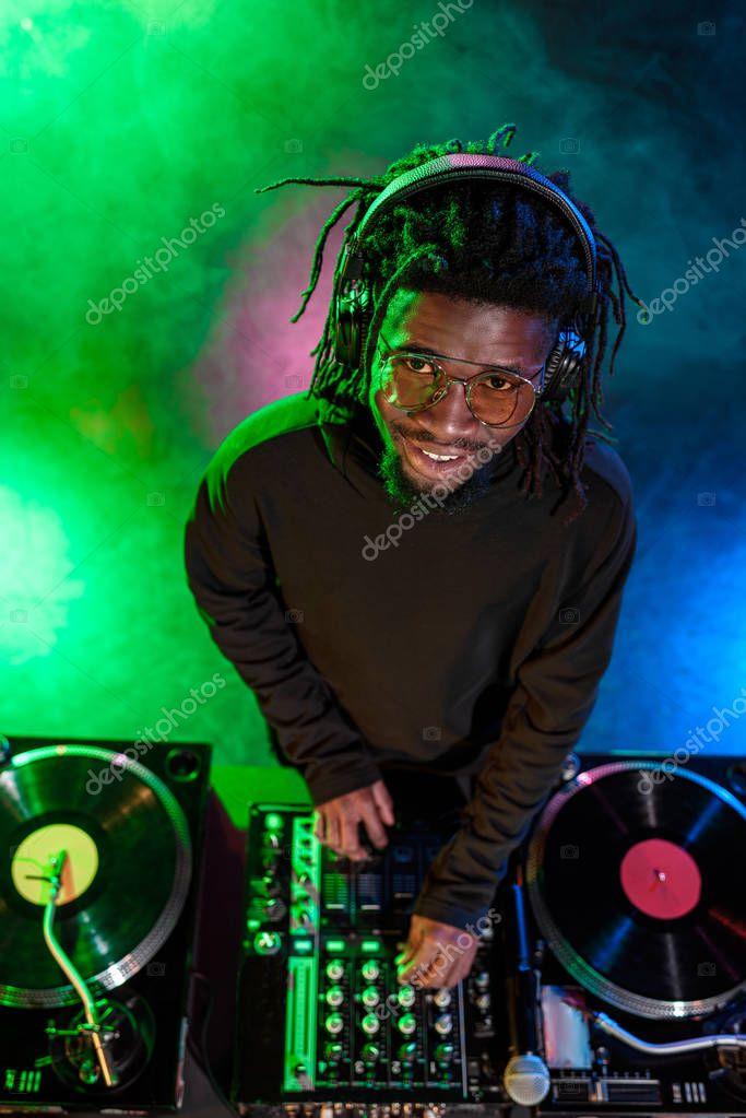 DJ with sound mixer in nightclub