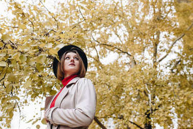 woman in trench coat and hat in park
