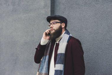 bearded man talking by phone