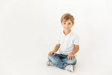 Adorable little boy sitting and smiling at camera isolated on white stock vector