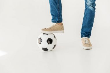 Low section of young man standing with soccer ball isolated on white stock vector