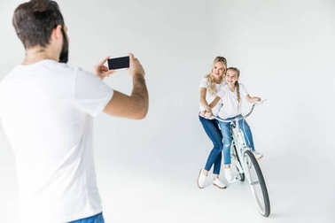 man photographing family with smartphone