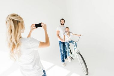 woman photographing family with smartphone