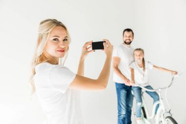 Happy young woman photographing family with smartphone isolated on white stock vector