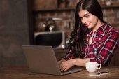 Mädchen mit Laptop, Smartphone und Kaffee