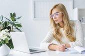 Fotografie blond podnikatelka psaní a workig s notebookem