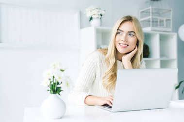 dreamy businesswoman working with laptop