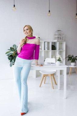 stylish businesswoman posing in office