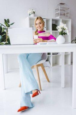 stylish businesswoman sitting at workplace