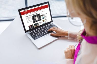 Cropped view of woman using laptop with bbc news website stock vector