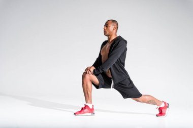 athletic young african american sportsman stretching and looking away on grey