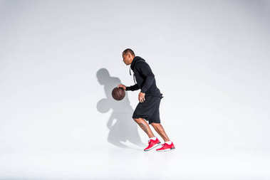 full length view of young african american sportsman playing with basketball ball on grey