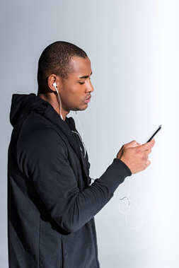 side view of young african american man using smartphone on grey