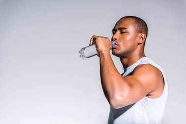 young african american sportsman drinking water from bottle isolated on grey