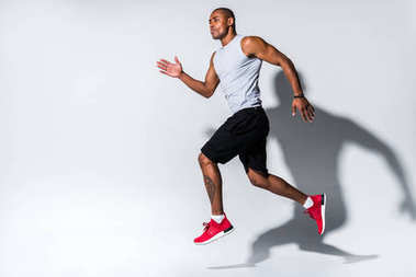 athletic young african american sportsman running on grey
