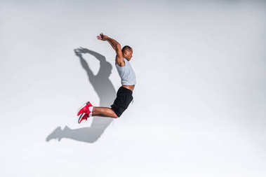side view of young african american sportsman jumping on grey