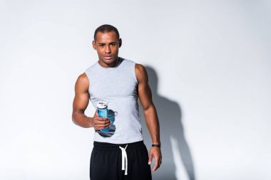 young african american sportsman holding sports bottle with water and looking at camera on grey