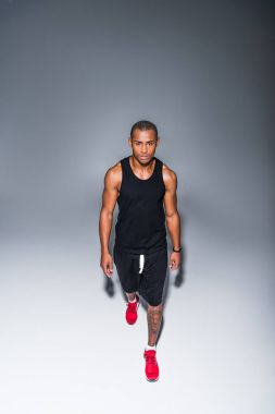 high angle view of young african american sportsman walking on grey