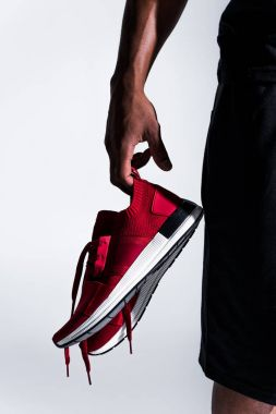 close-up partial view of african american sportsman holding sports shoes isolated on grey