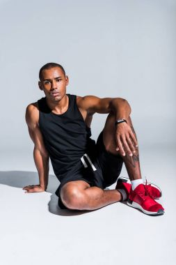 young african american sportsman wearing fitness tracker and looking at camera on grey