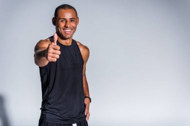 cheerful african american sportsman showing thumb up and smiling at camera isolated on grey