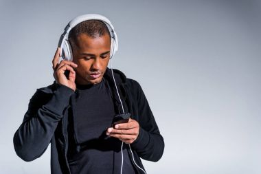 handsome young african american man in headphones using smartphone isolated on grey