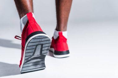 selective focus of african american sportsman in sneakers on grey