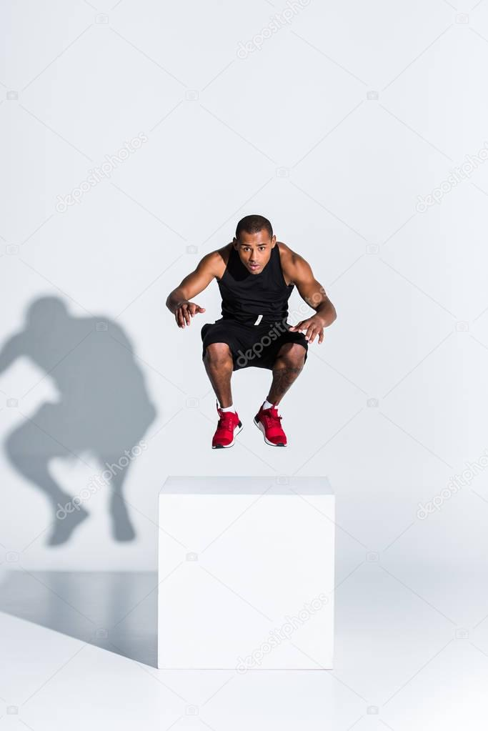 young african american sportsman jumping and looking at camera on grey
