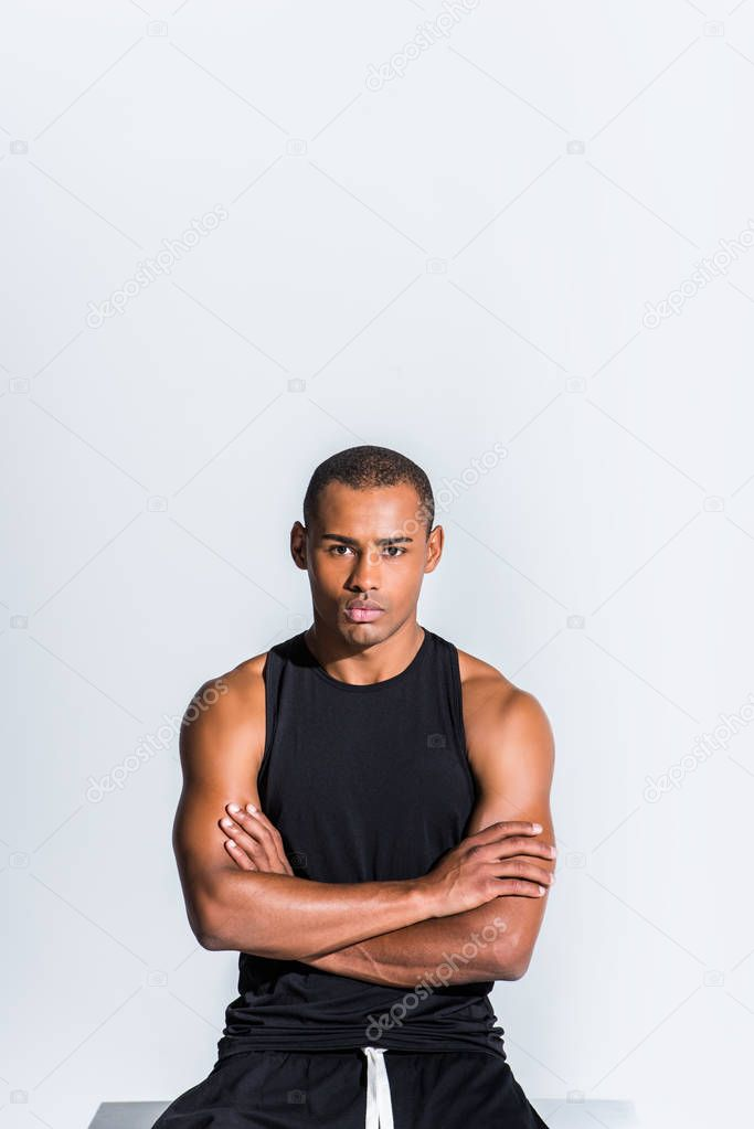 confident young african american sportsman with crossed arms looking at camera isolated on grey